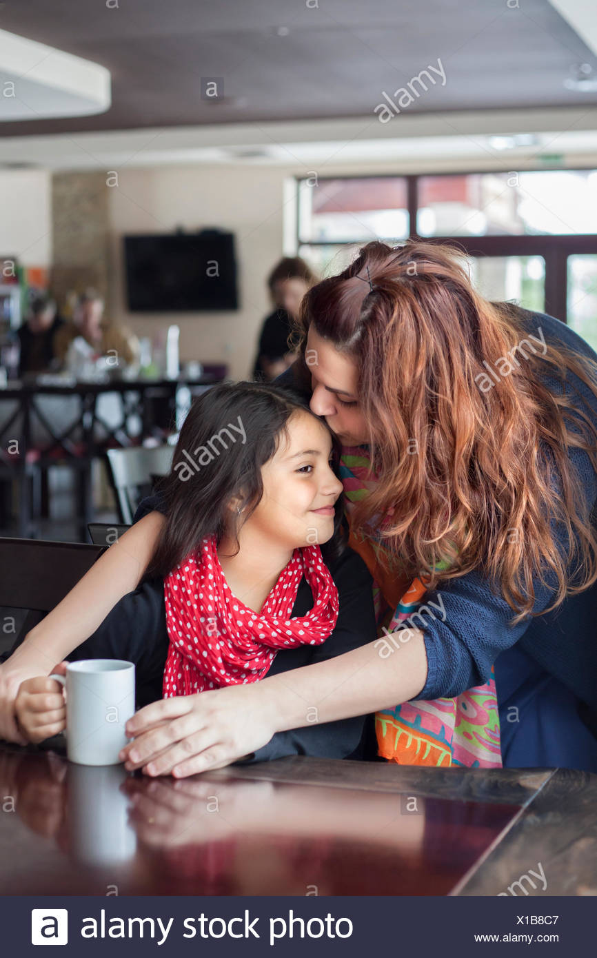 Mother kissing daughter (6-7) on forehead in cafe - Stock Image