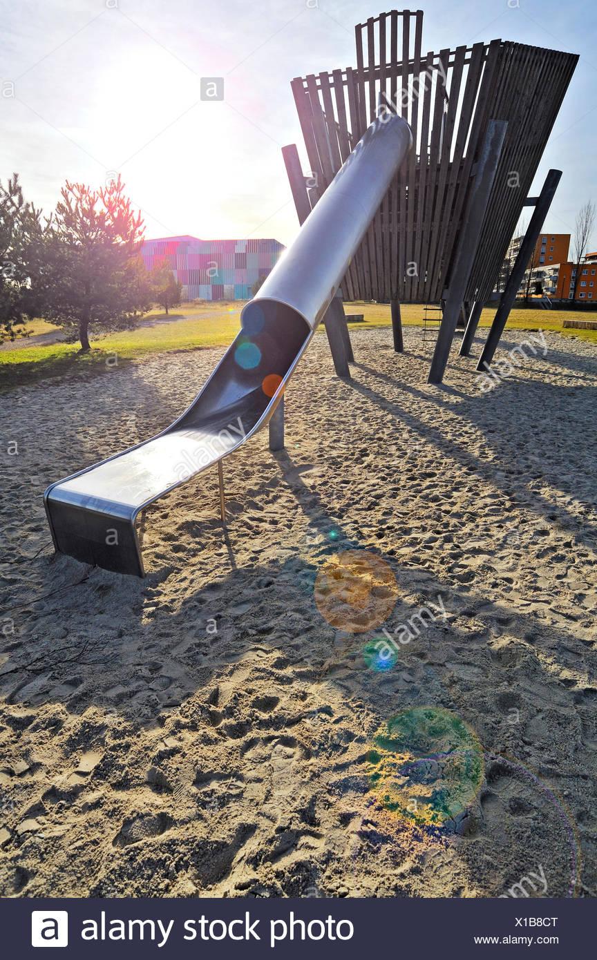 Slide on a playground, back lit - Stock Image
