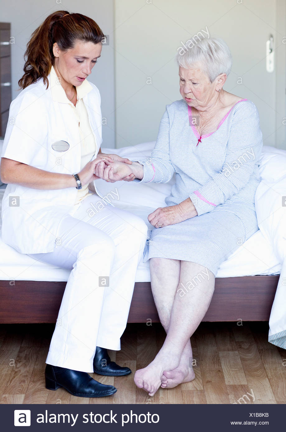A senior woman having her pulse checked by a nurse - Stock Image
