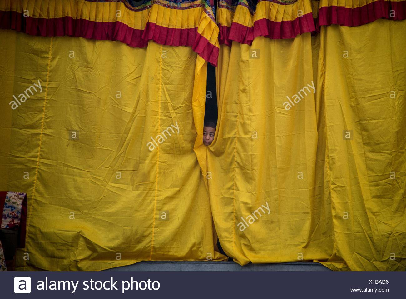 Nepal, Bodnath, monk behind curtain of Boudhanath temple - Stock Image