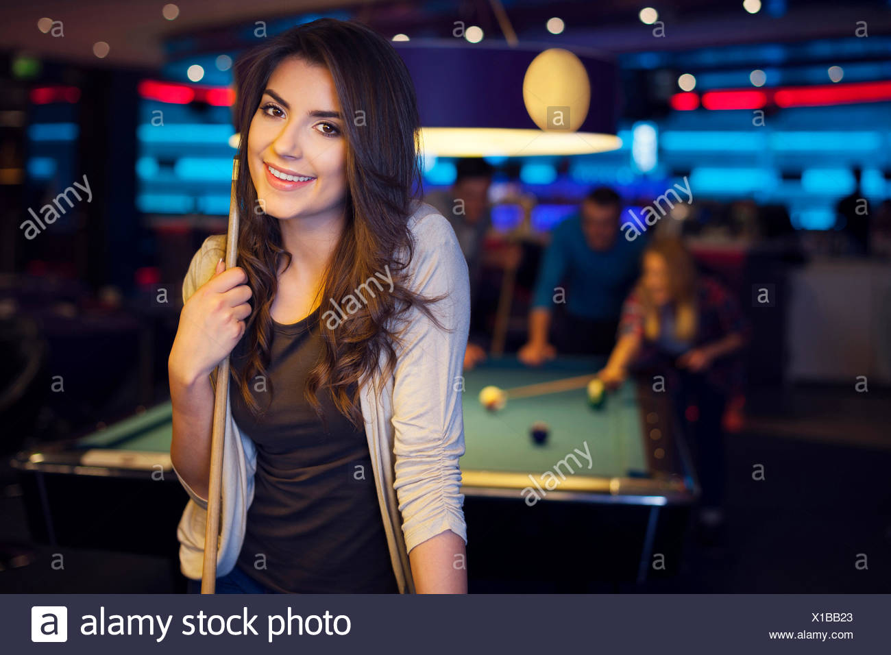 Friends hanging out at the pool hall - Stock Image