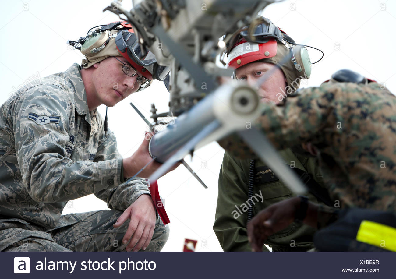 Airman 1st Class Gerald Rascoe helps Marine Corps ordnance technicians load a missile Nov. 4, 2013, at Kunsan Air Base, South Stock Photo