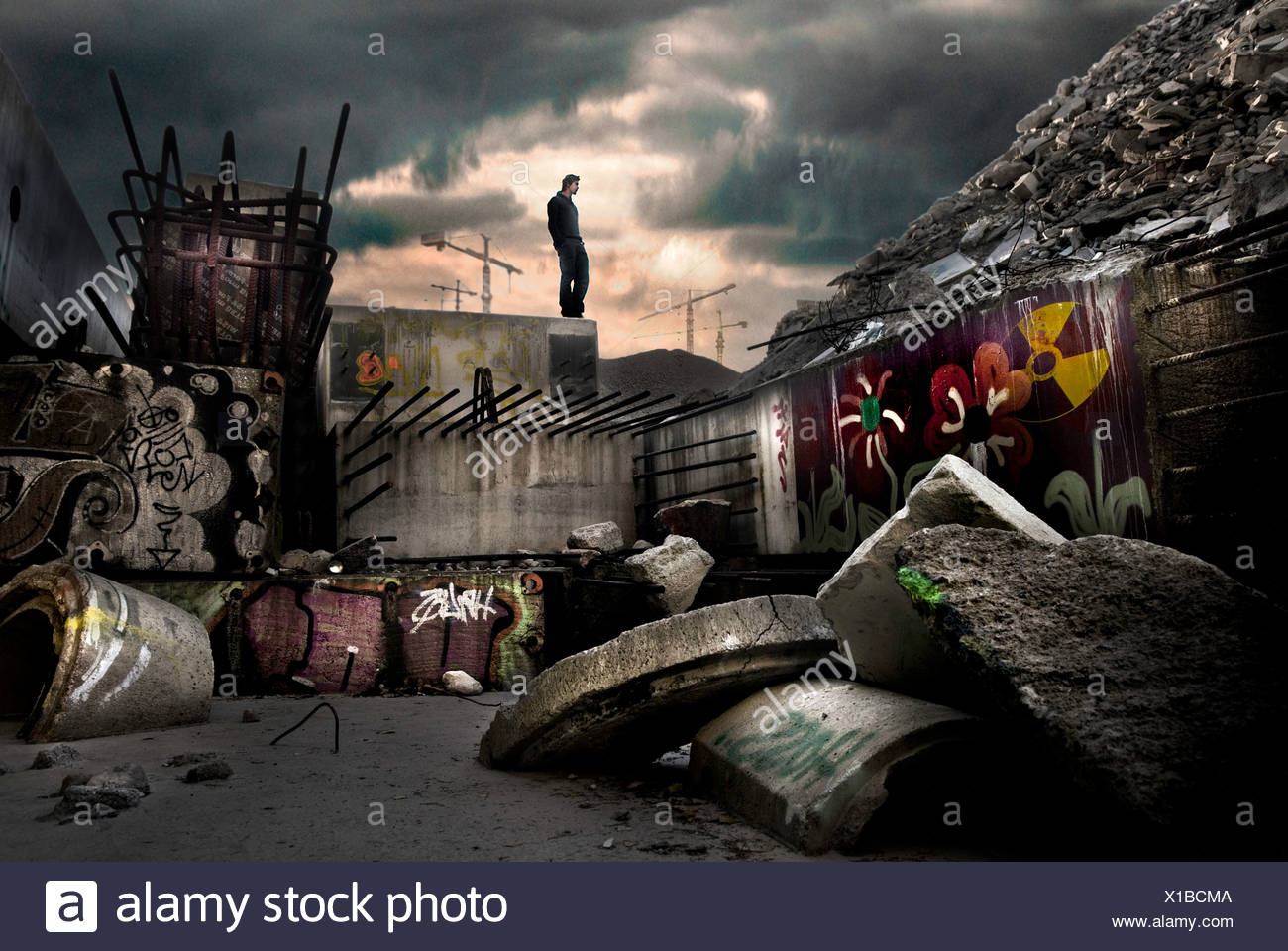 Young male figure standing on concrete block by rubbish tip - Stock Image