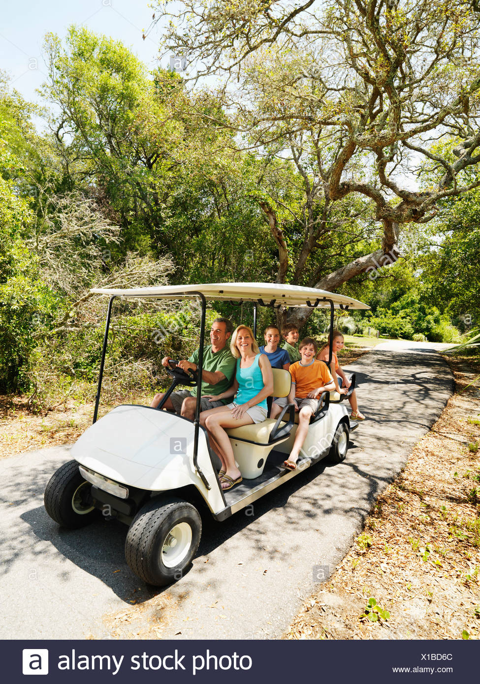 Caucasian family riding on golf cart on trail in North Carolina USA on
