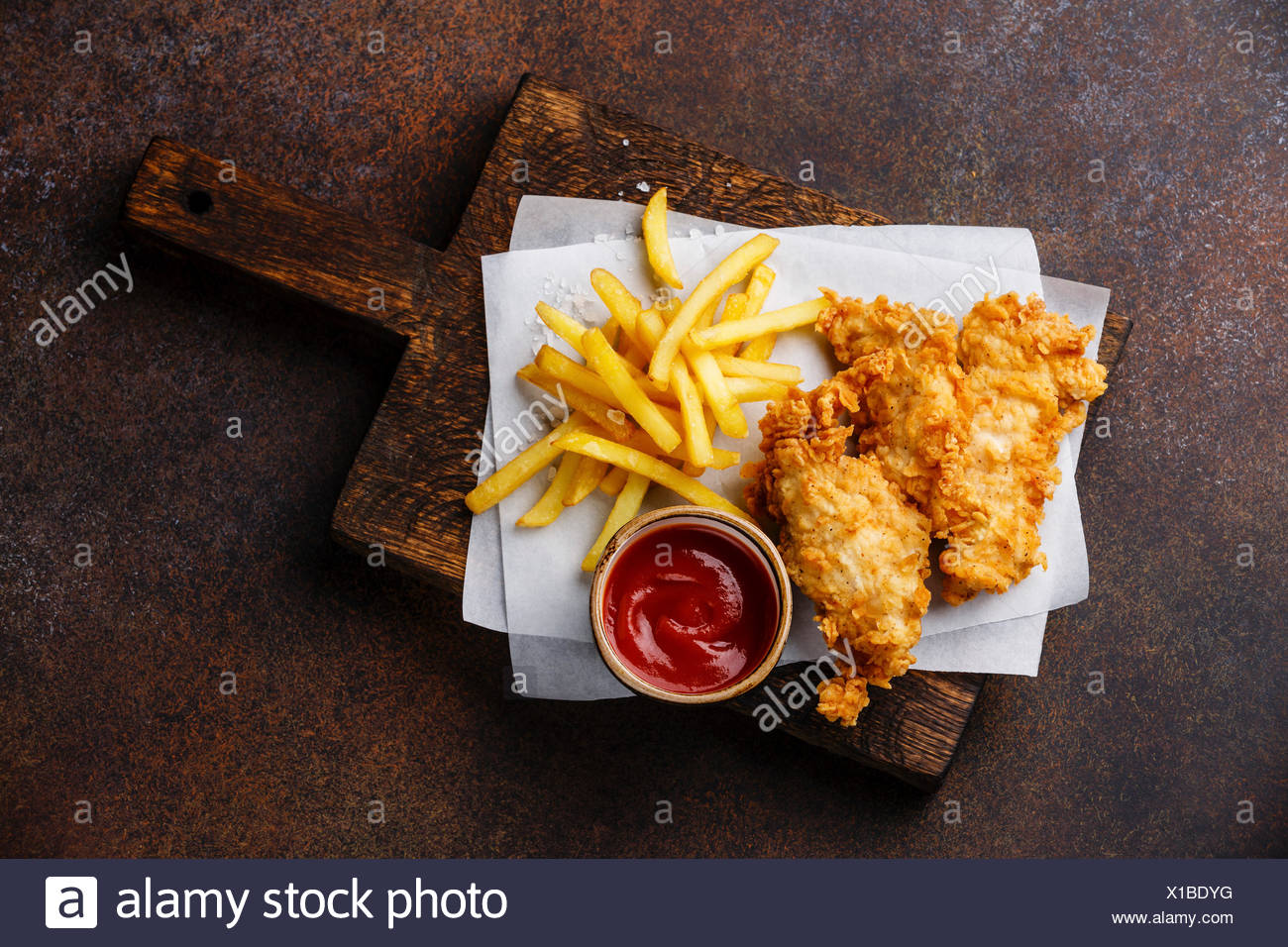 Fish and Chips british fast food with ketchup sauce on dark background Stock Photo