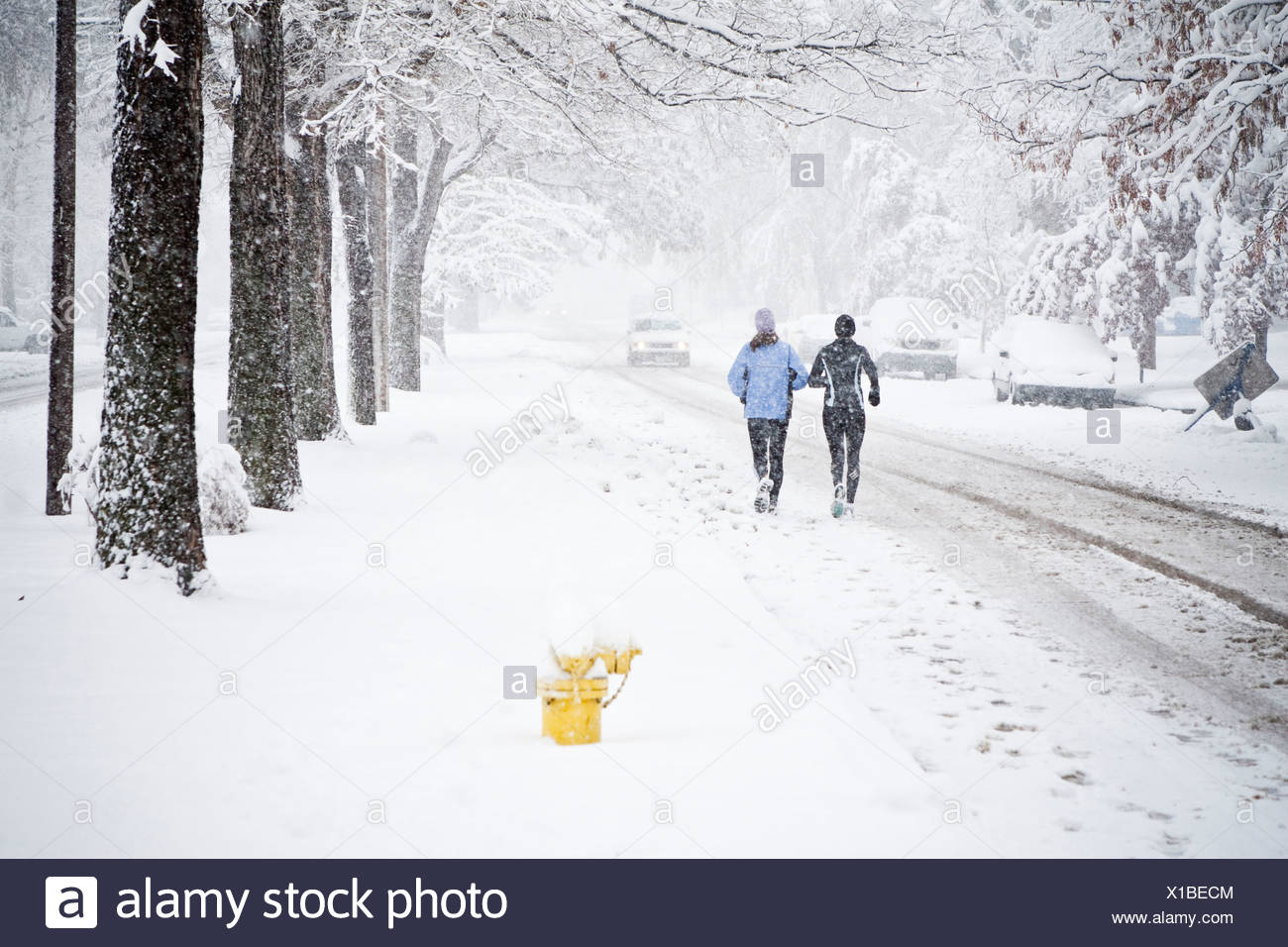 Two women run down Mountain Avenue in a snowstorm. - Stock Image