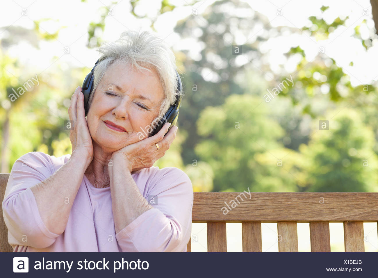 Woman listening to music using headphones with her head tilted - Stock Image