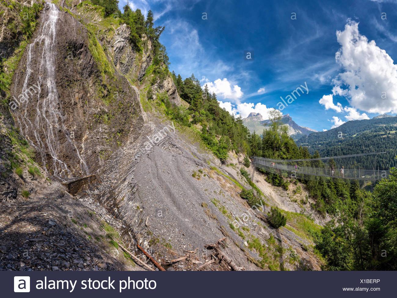 Bisse du Torrent Neuf Bisse wandering suspension bridge bridge landscape water summer mountains hills people waterfall Saviese - Stock Image