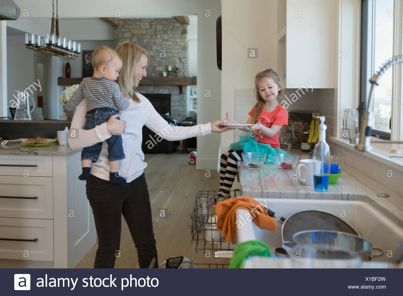 Daughter helping mother do dishes in kitchen - Stock Image