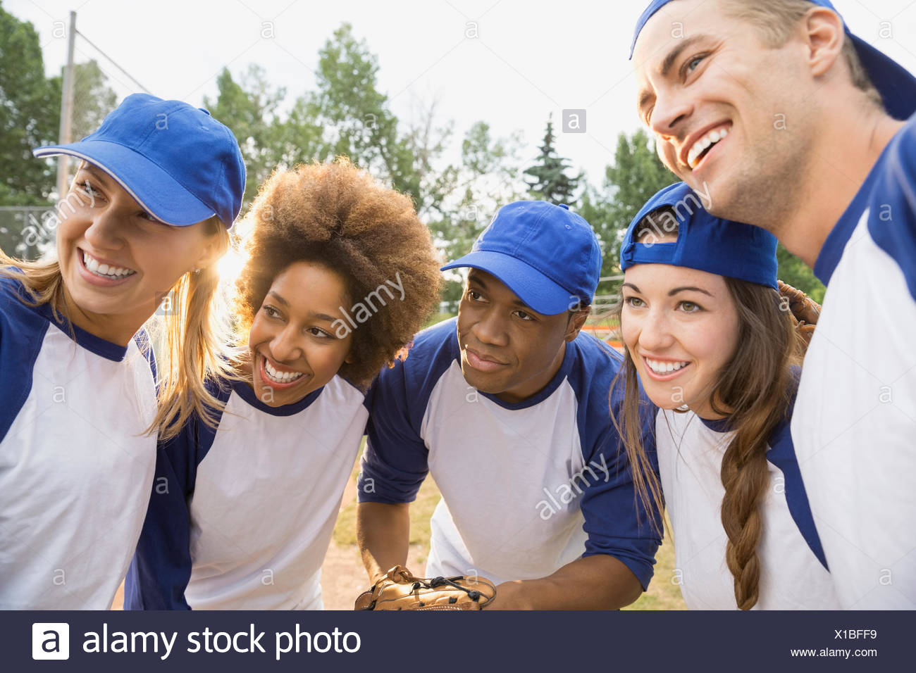 Baseball players talking in huddle on field - Stock Image
