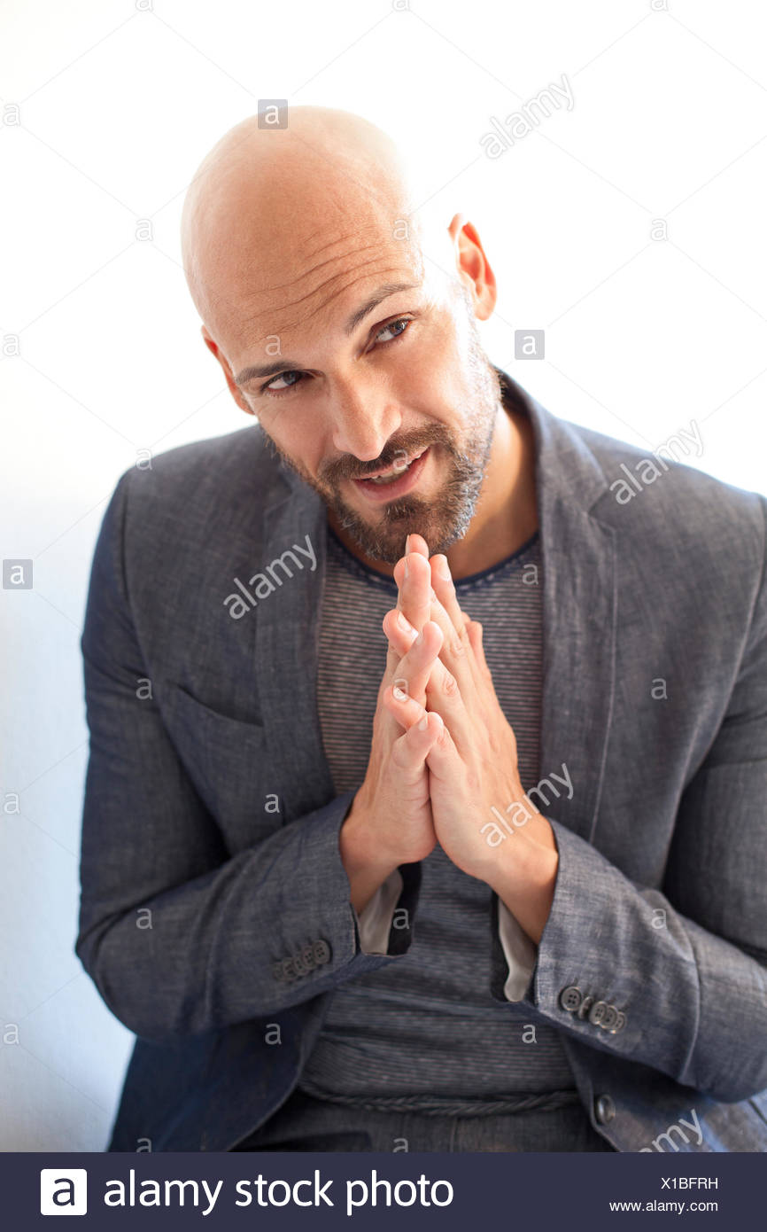 Portrait of bald man in grey suit asking for forgiveness - Stock Image