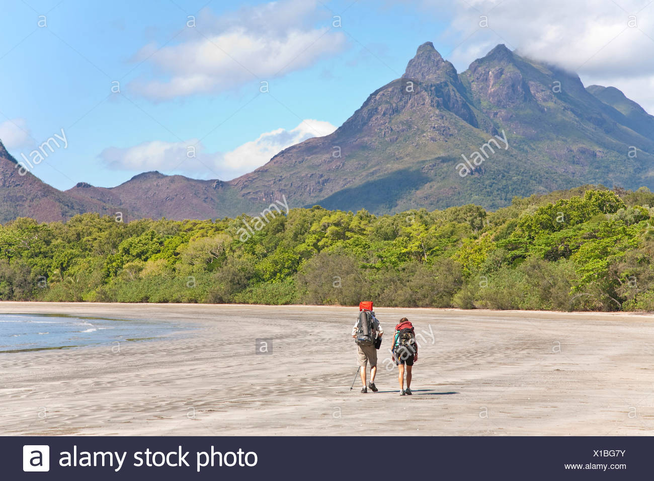 A man and woman with their baby hike along Zoe Bay, Hinchinbrook Island, Queensland, Australia. - Stock Image