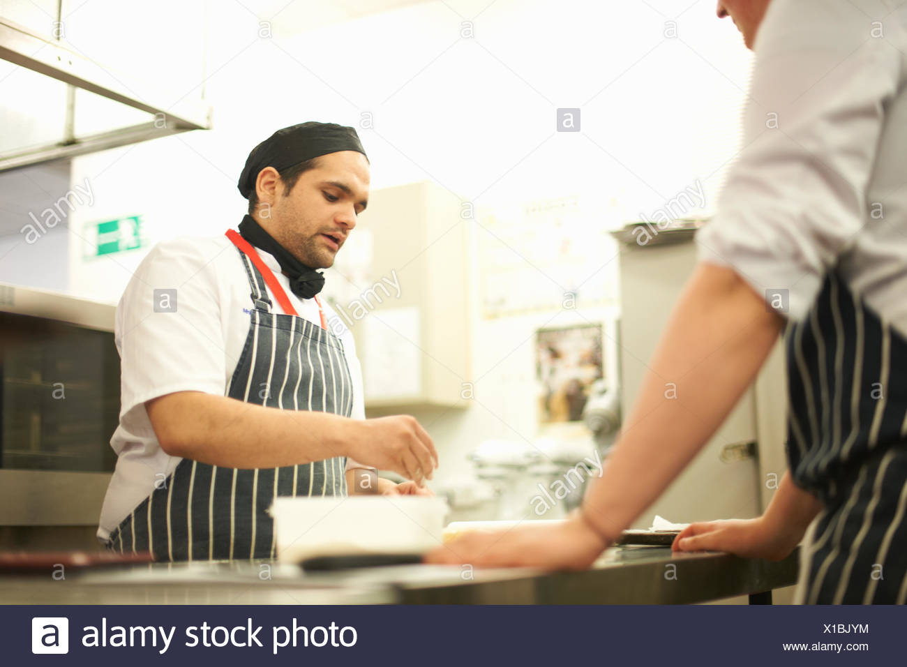 Chef lecturer demonstrating food preparation to teenage catering student at kitchen counter - Stock Image