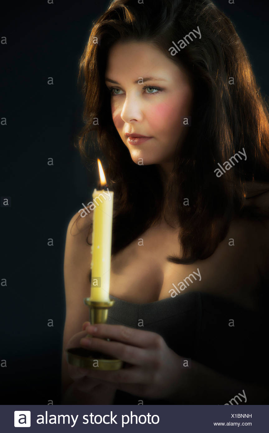 Young woman holding candle - Stock Image