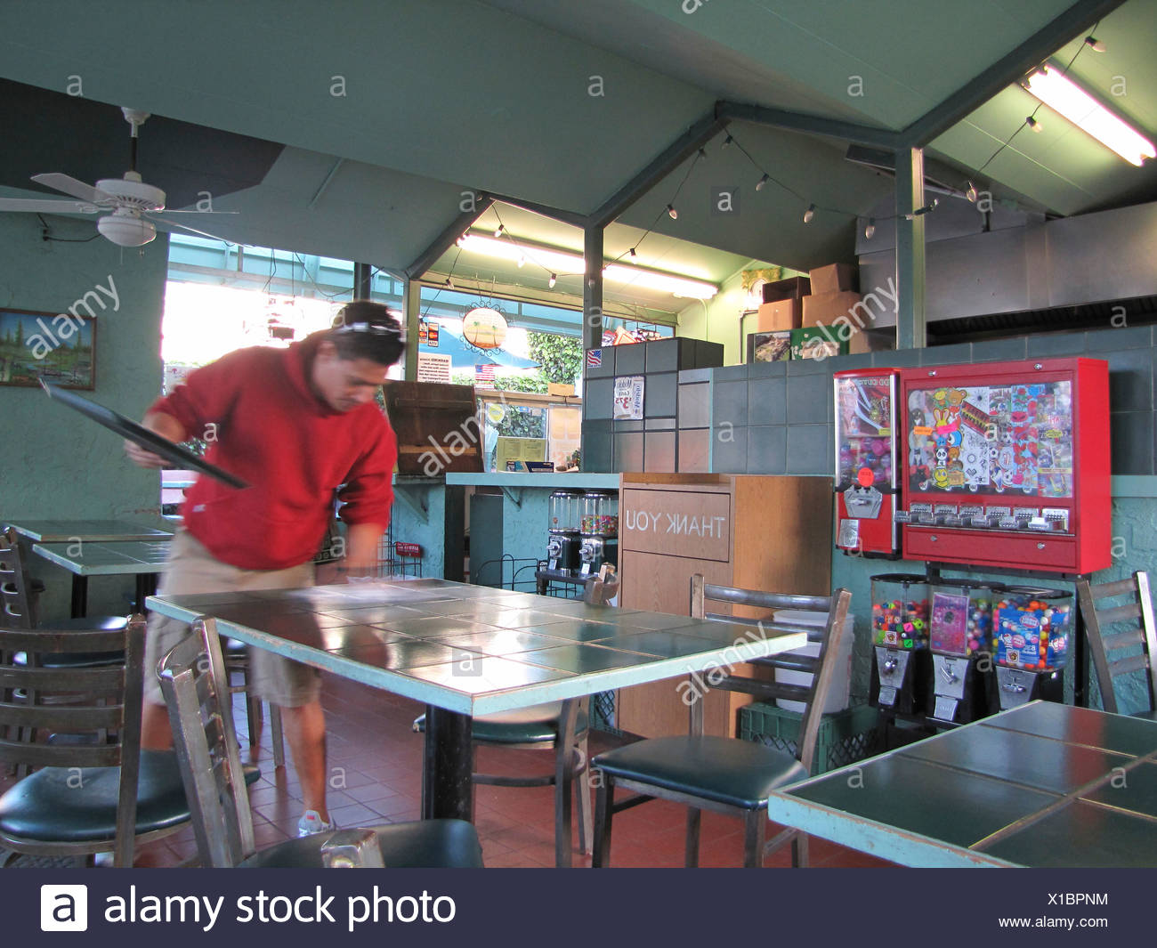 Man cleaning table in American fast food restaurant, chewing-gum machine in the left of the image, USA, California, Santa Cruz - Stock Image