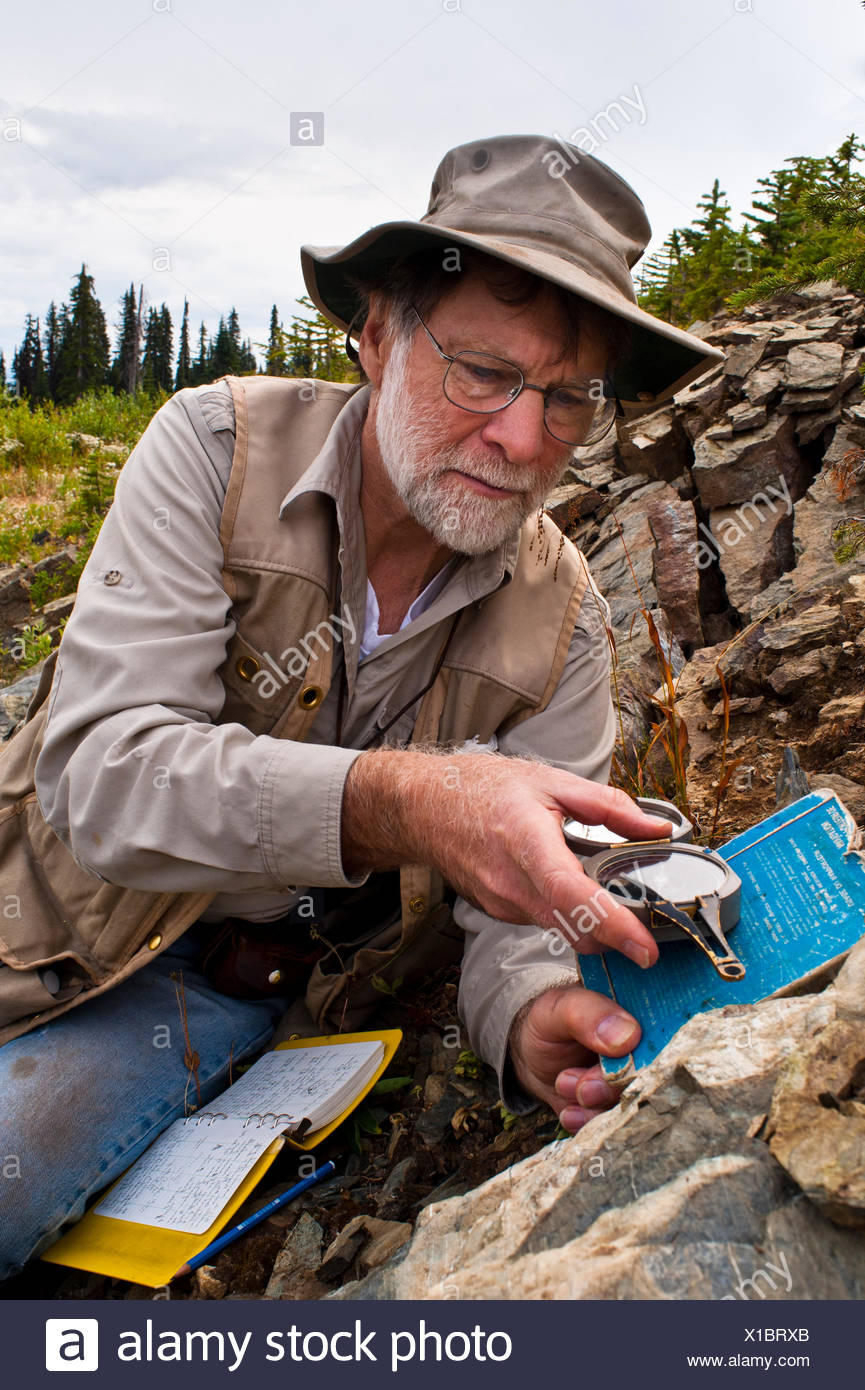 A geologist measures strike and dip of a rock outcrop durring a mineral exploration program,  British Columbia, Canada - Stock Image