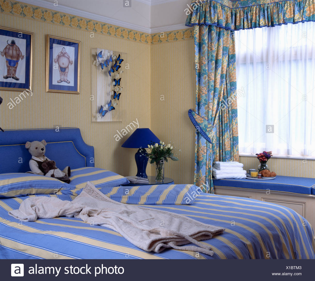 Blue Patterned Curtains And Striped Bed Linen In Yellow Bedroom Stock Photo Alamy