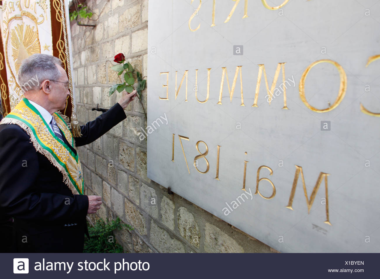 Freemason placing a rose on the Mur des Federes in the Pere Lachaise cemetery (commemorating the victims of the 1871 Paris Commu - Stock Image