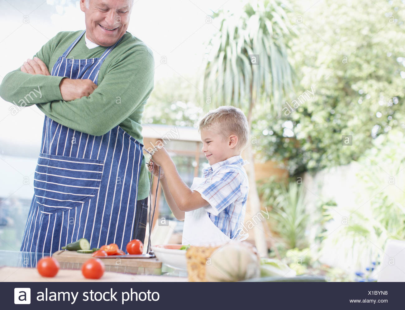 Grandson tying apron for grandfather - Stock Image