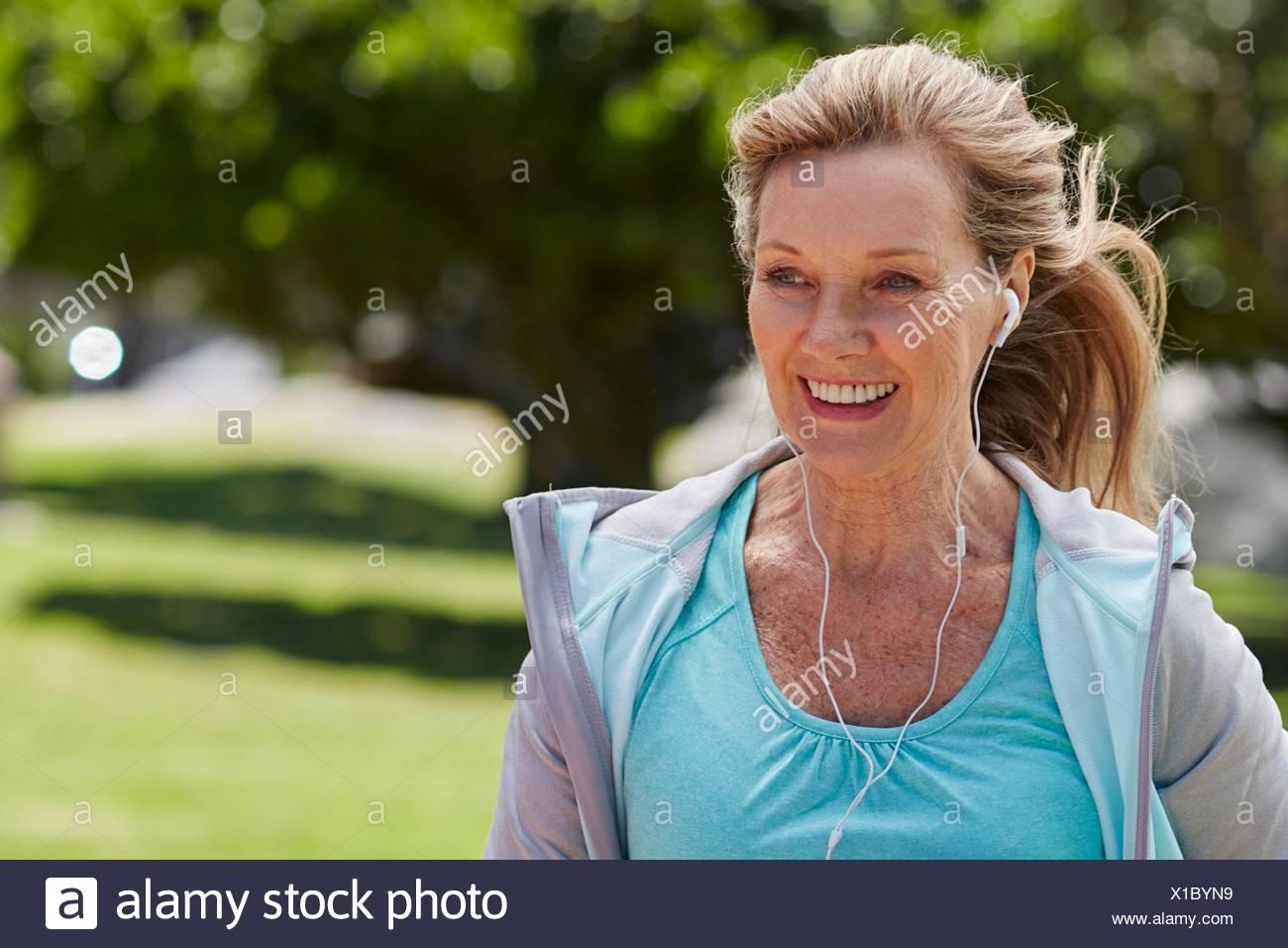 MODEL RELEASED. Senior woman exercising wearing earphones. - Stock Image
