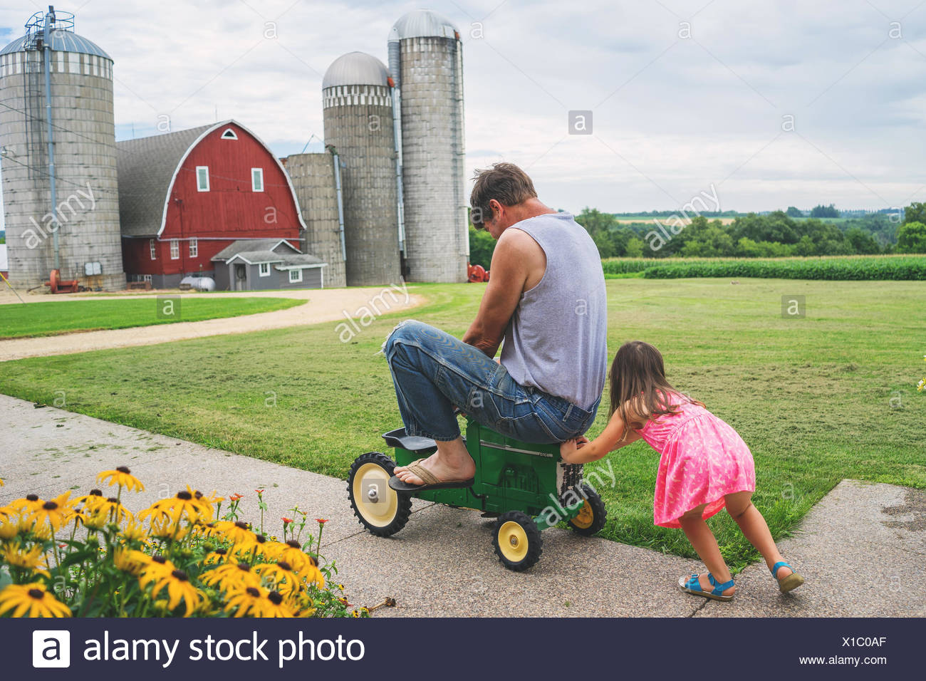 Girl pushing her father on a toy tractor - Stock Image