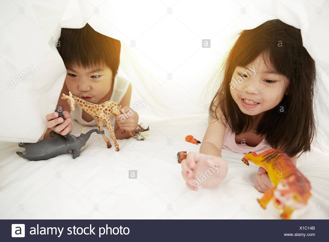 Young Chinese boy and girl in bed playing with their toys under the bedsheets - Stock Image