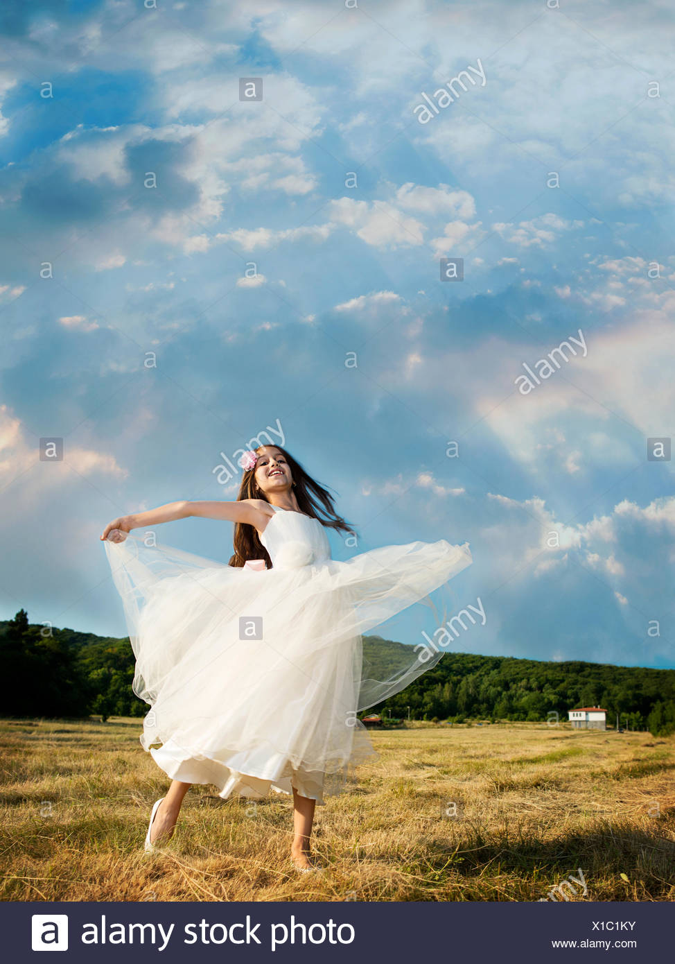 vertical, outdoors, day, real people, one person, girls, one girl only, children, one child only, 8-9 years, elementary age, caucasian ethnicity, front view, full length, looking at camera, differential focus, standing, dressing up, holding hands, costume, Halloween, halloween costume, fairy costume - Stock Image