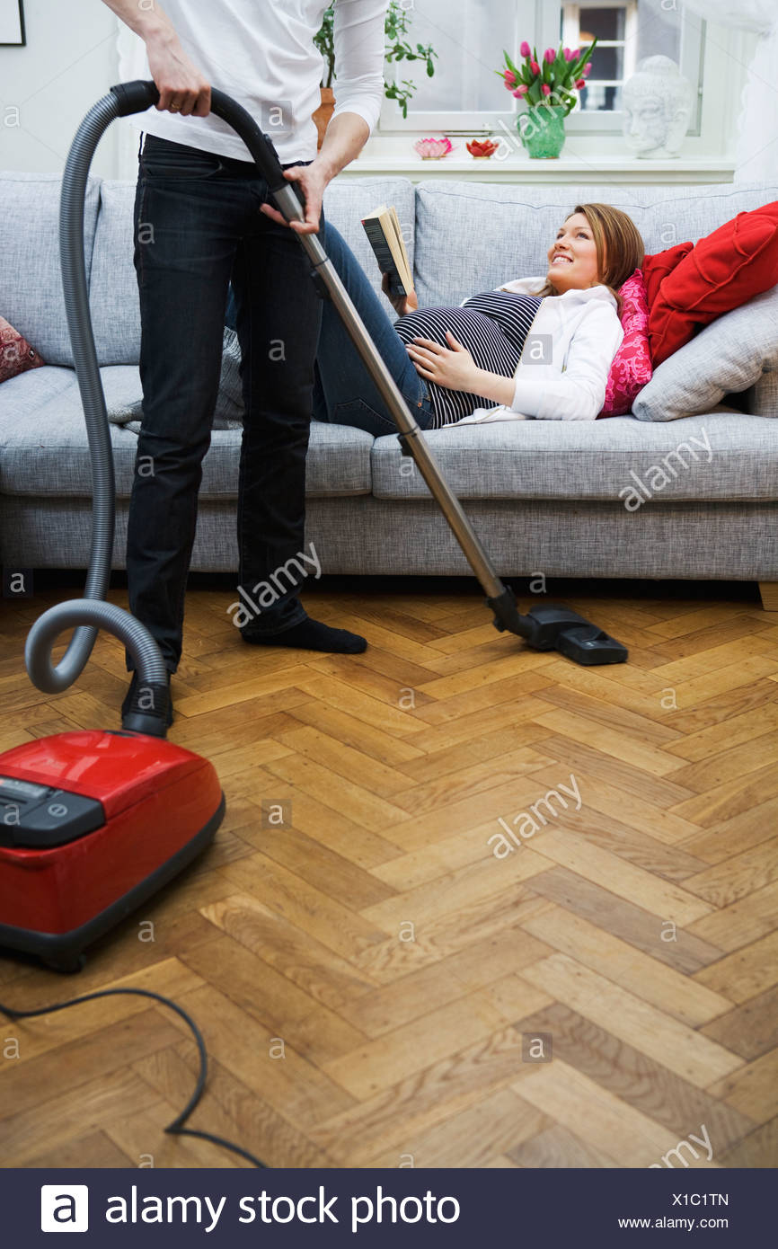 A pregnant woman lying on a couch and a man vacuuming Sweden. - Stock Image