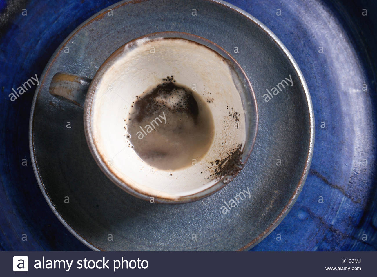 Blue ceramic cup of coffee grounds over blue ceramic tray. Top view. - Stock Image
