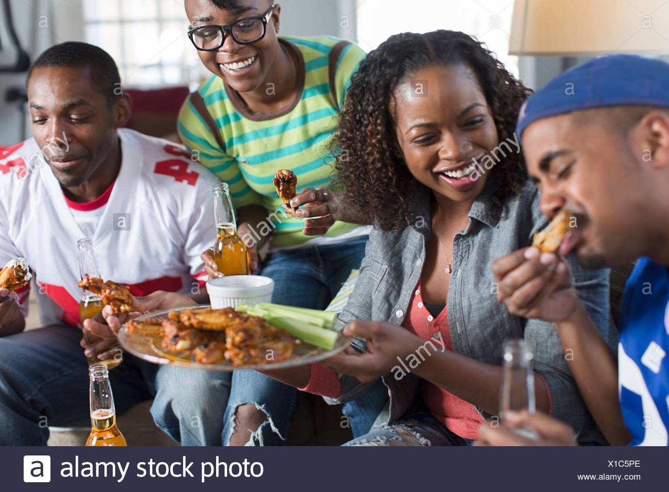 Group of adult friends eating takeaway on living room sofa - Stock Image