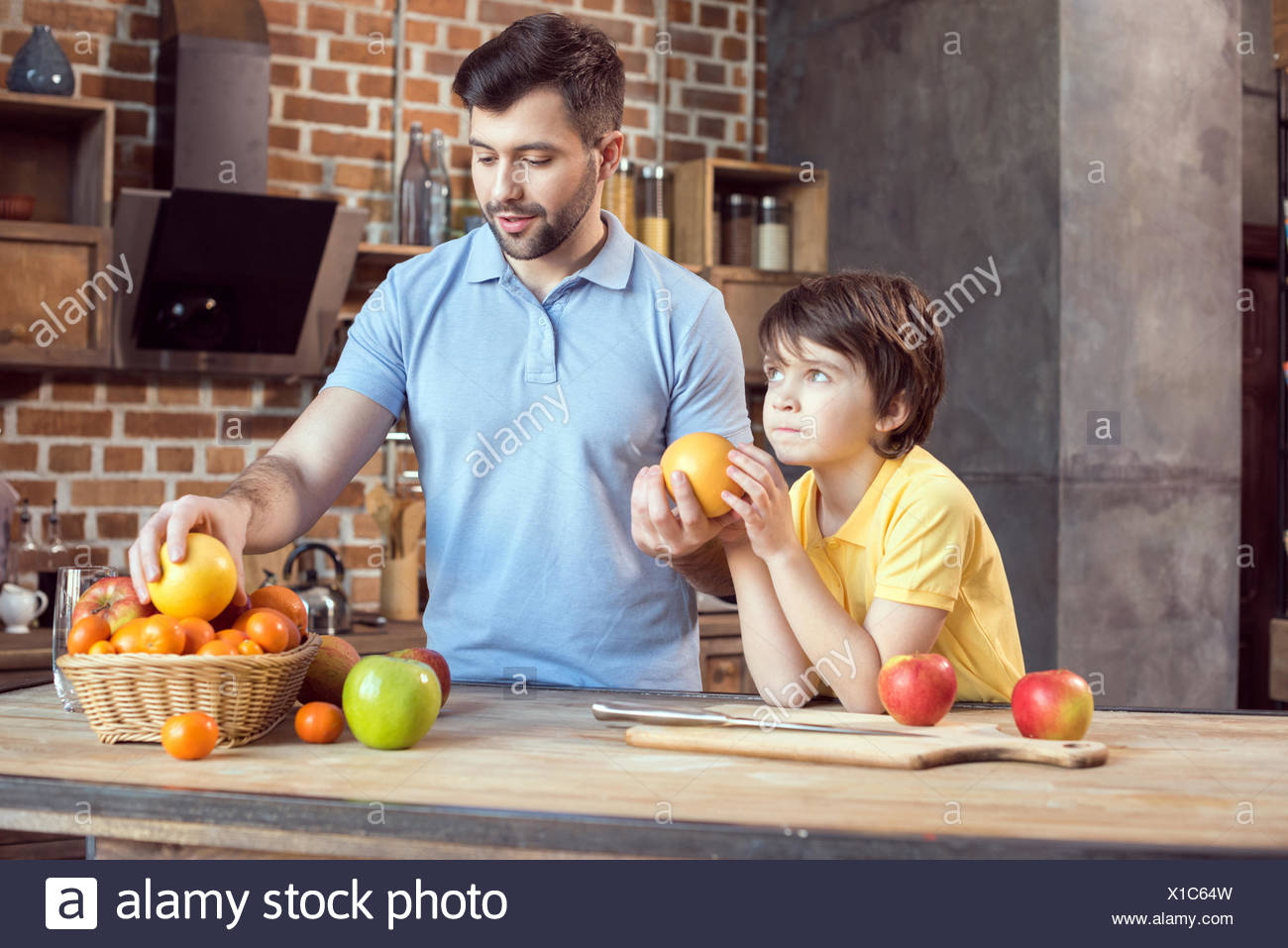 Father and son selecting fruits from basket at kitchen table - Stock Image