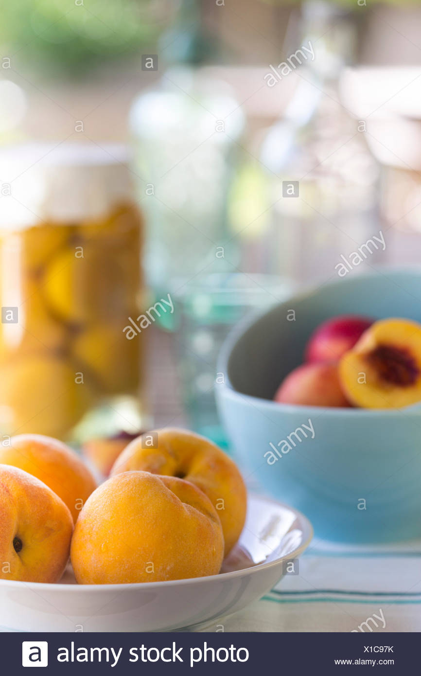 summer picnic of yellow peaches in a dish, with aqua bowls of nectarines and preserved peaches in background - Stock Image