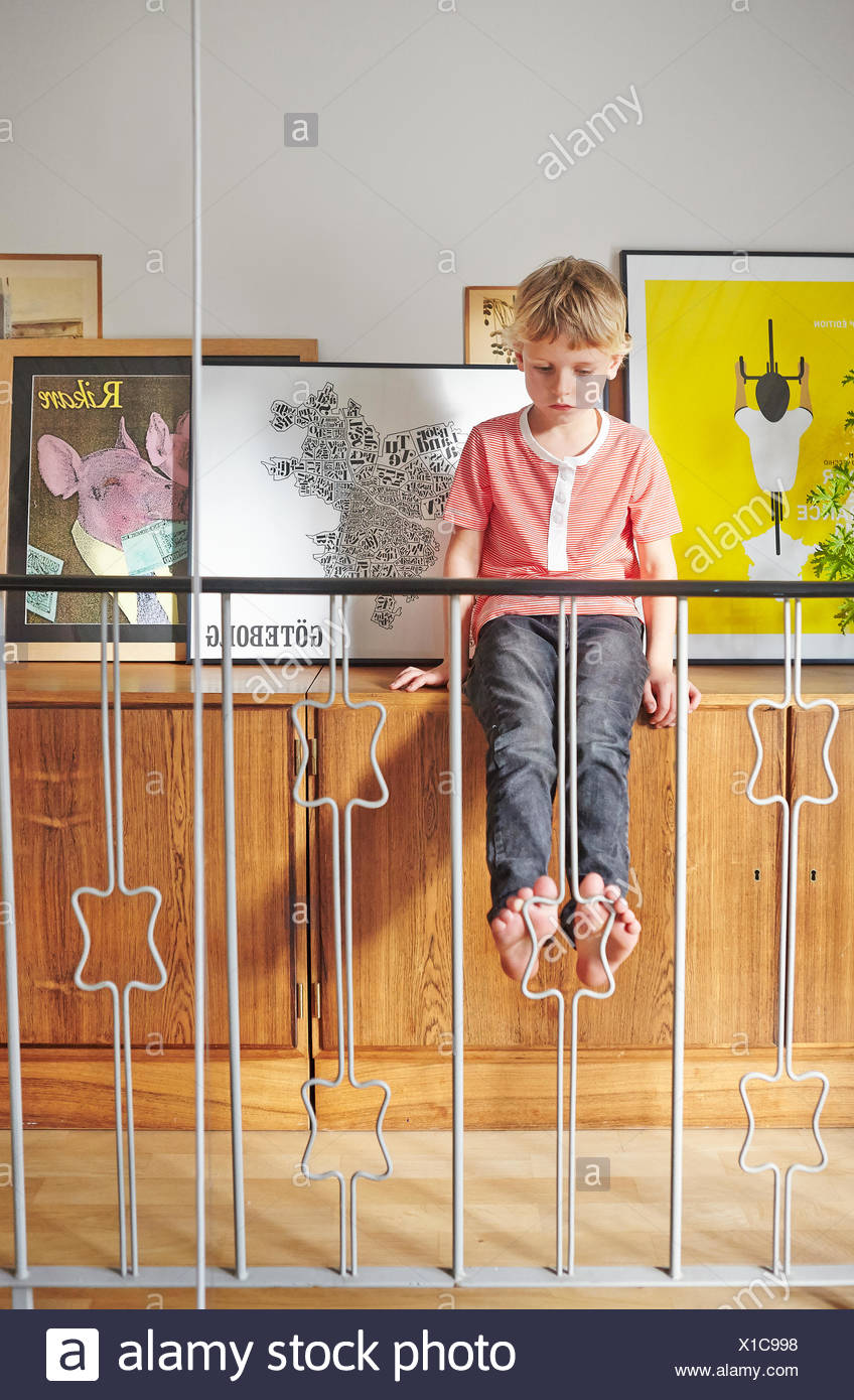 Boy sitting on cupboard with pictures behind railing - Stock Image