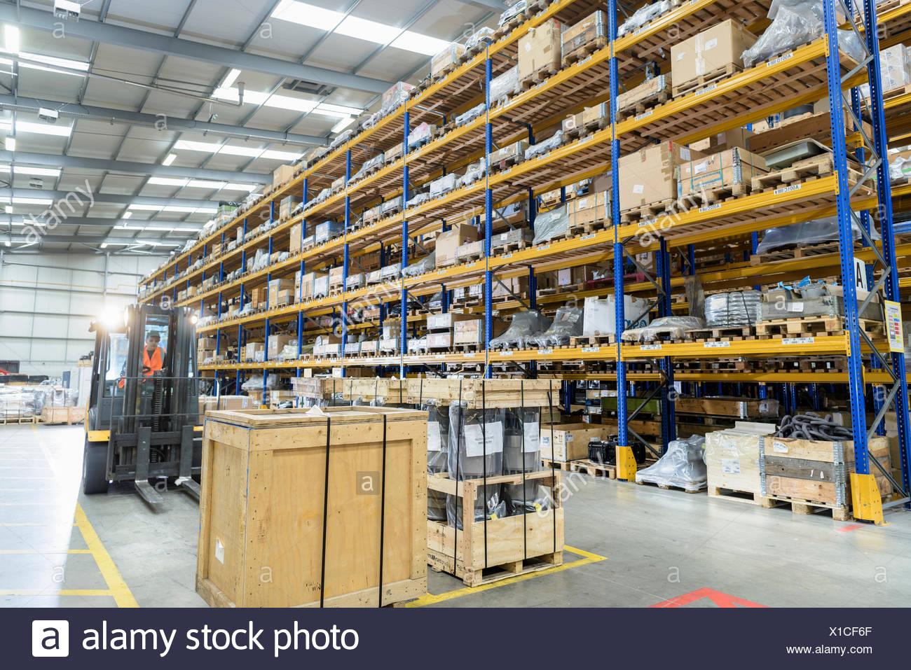 Female storage worker in train works warehouse - Stock Image