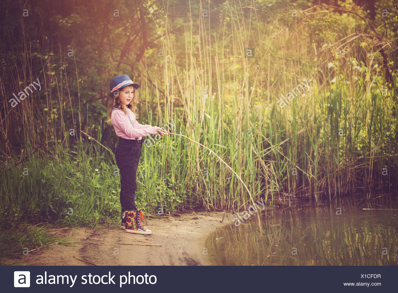 Girl fishing by the side of a lake - Stock Image