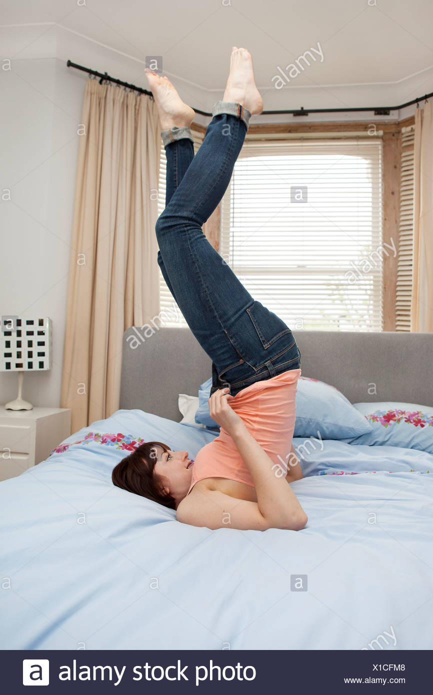 Young woman struggling to zip jeans on bed - Stock Image