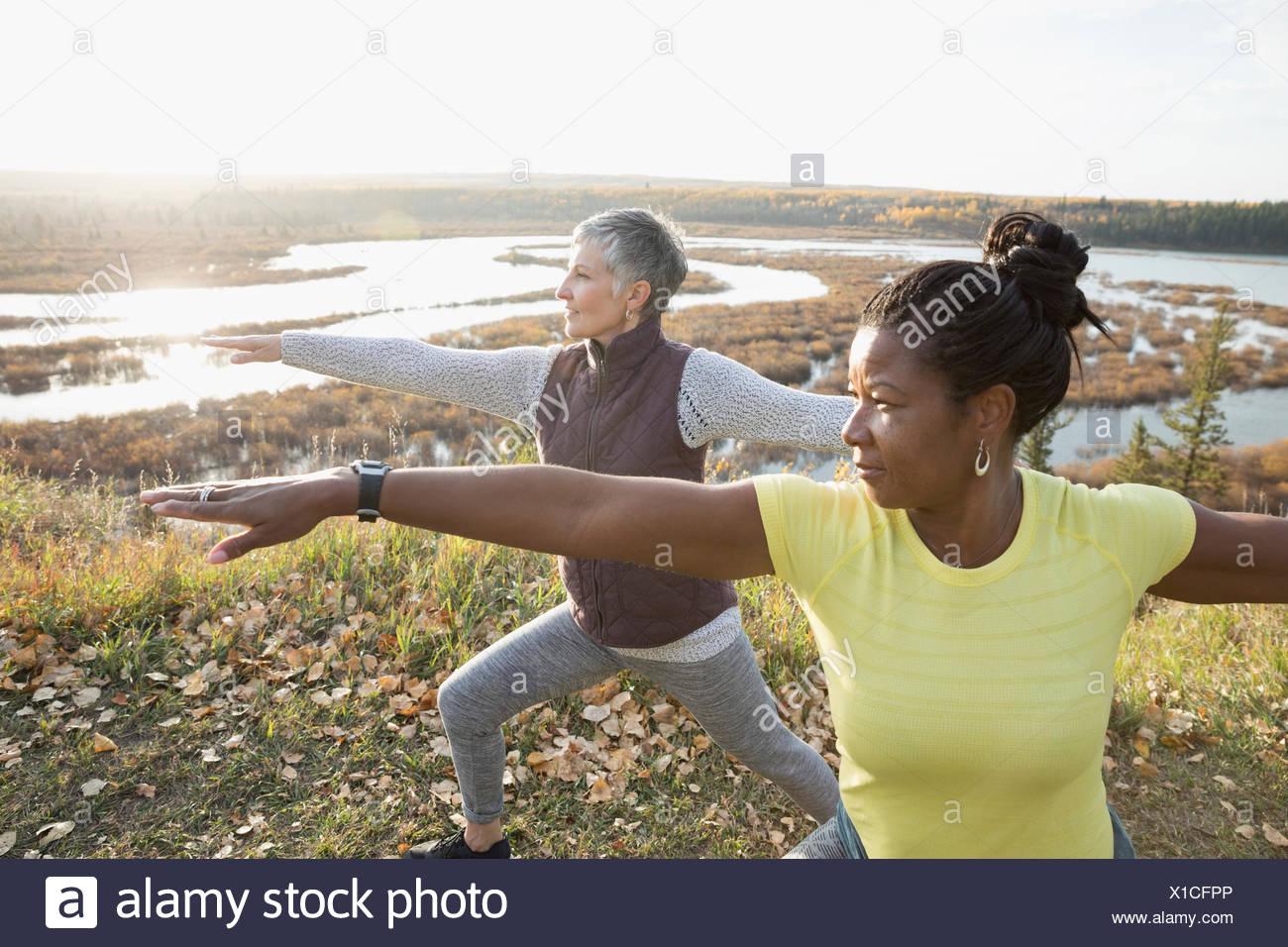 Women practicing yoga warrior 2 pose on autumn hilltop overlooking lake Stock Photo
