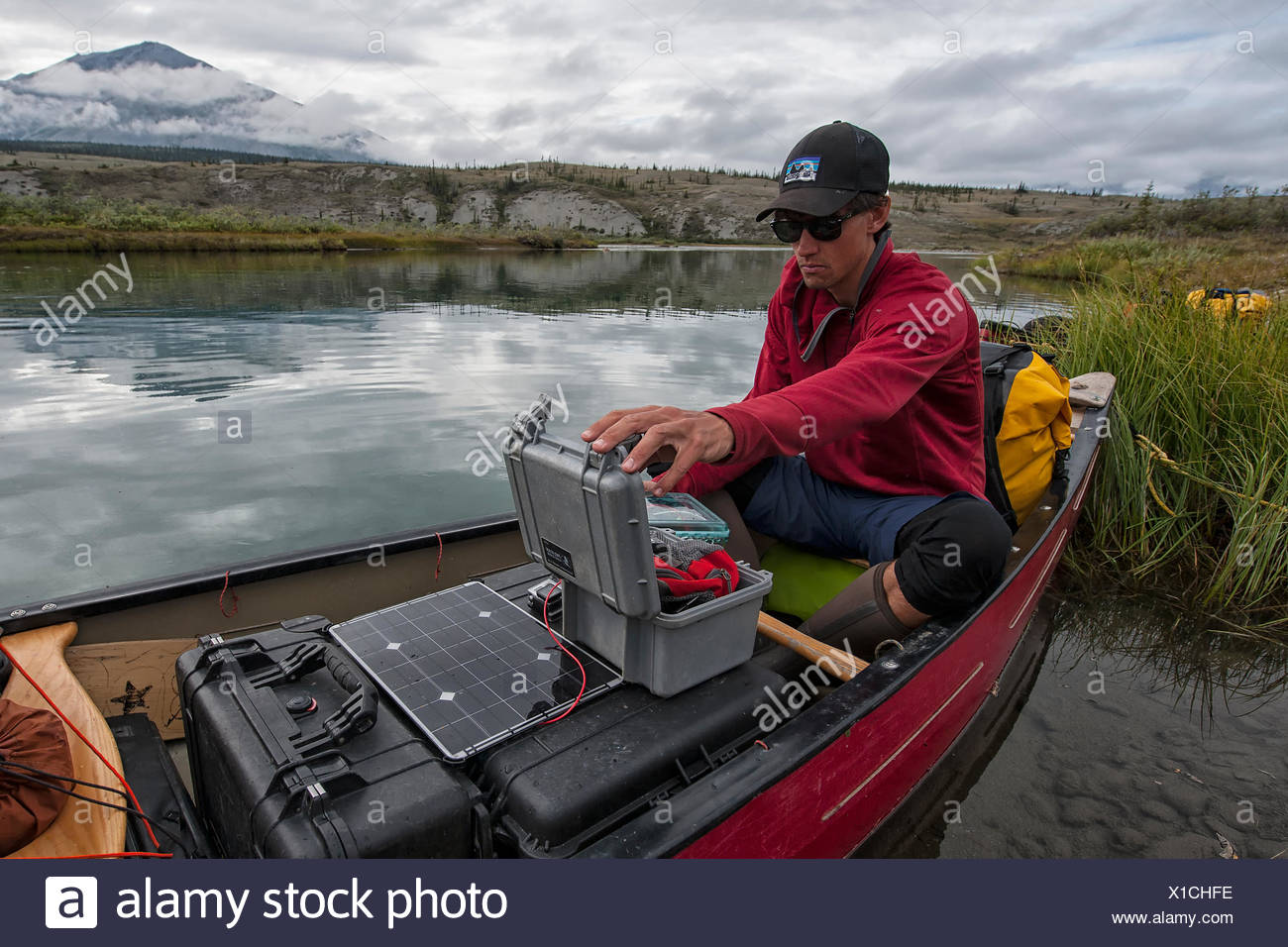 Videographer filming on the Wind River. Also, charging batteries using a solar charging system from our sponsors at Voltaic Systems. Pelican cases were critical for all the equipment, in case a canoe tipped. - Stock Image
