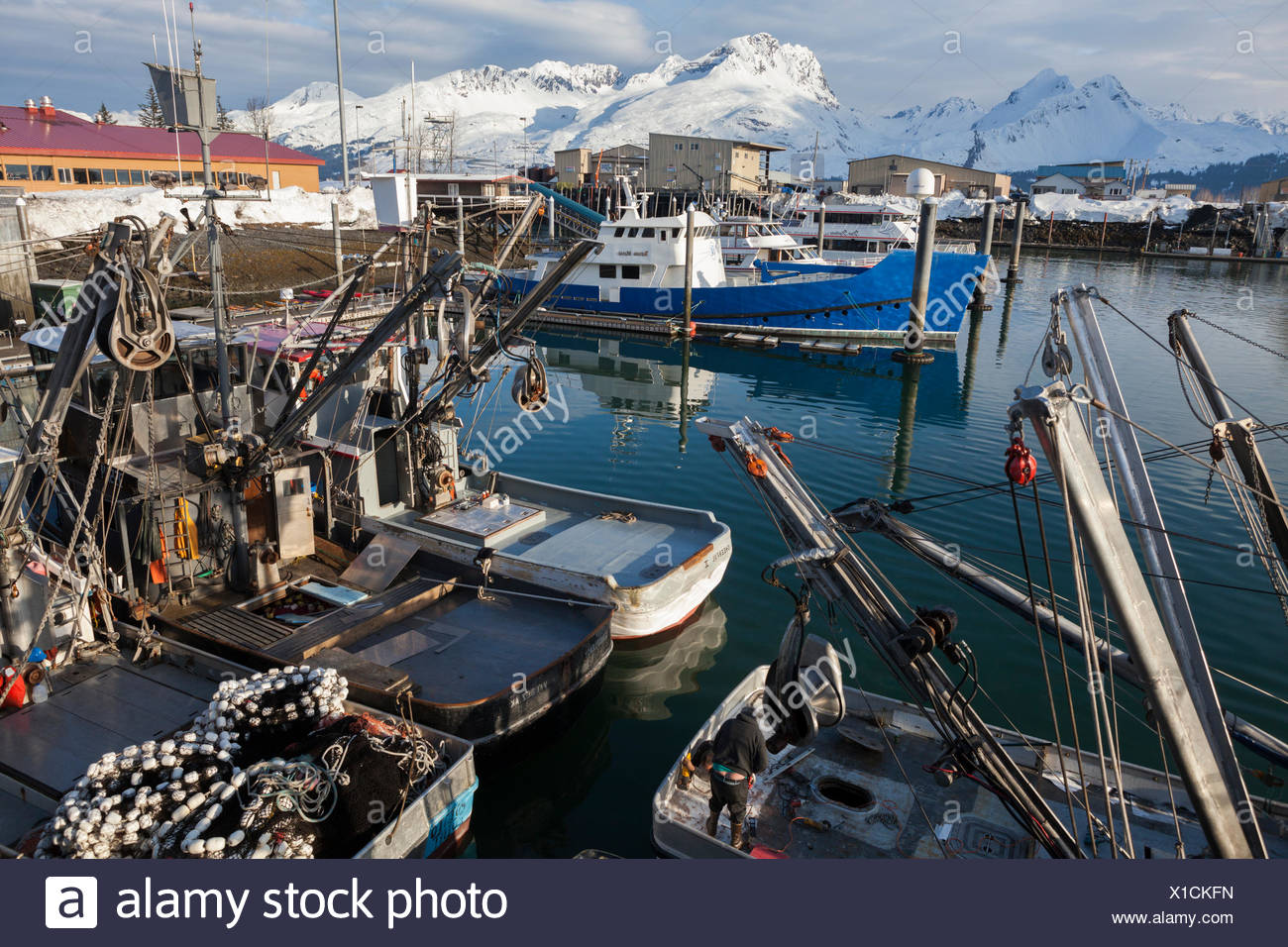 Fishing boats moored at the harbor in Valdez, Alaska. Peaks of the Chugach Mountains are visible across the fjord. - Stock Image