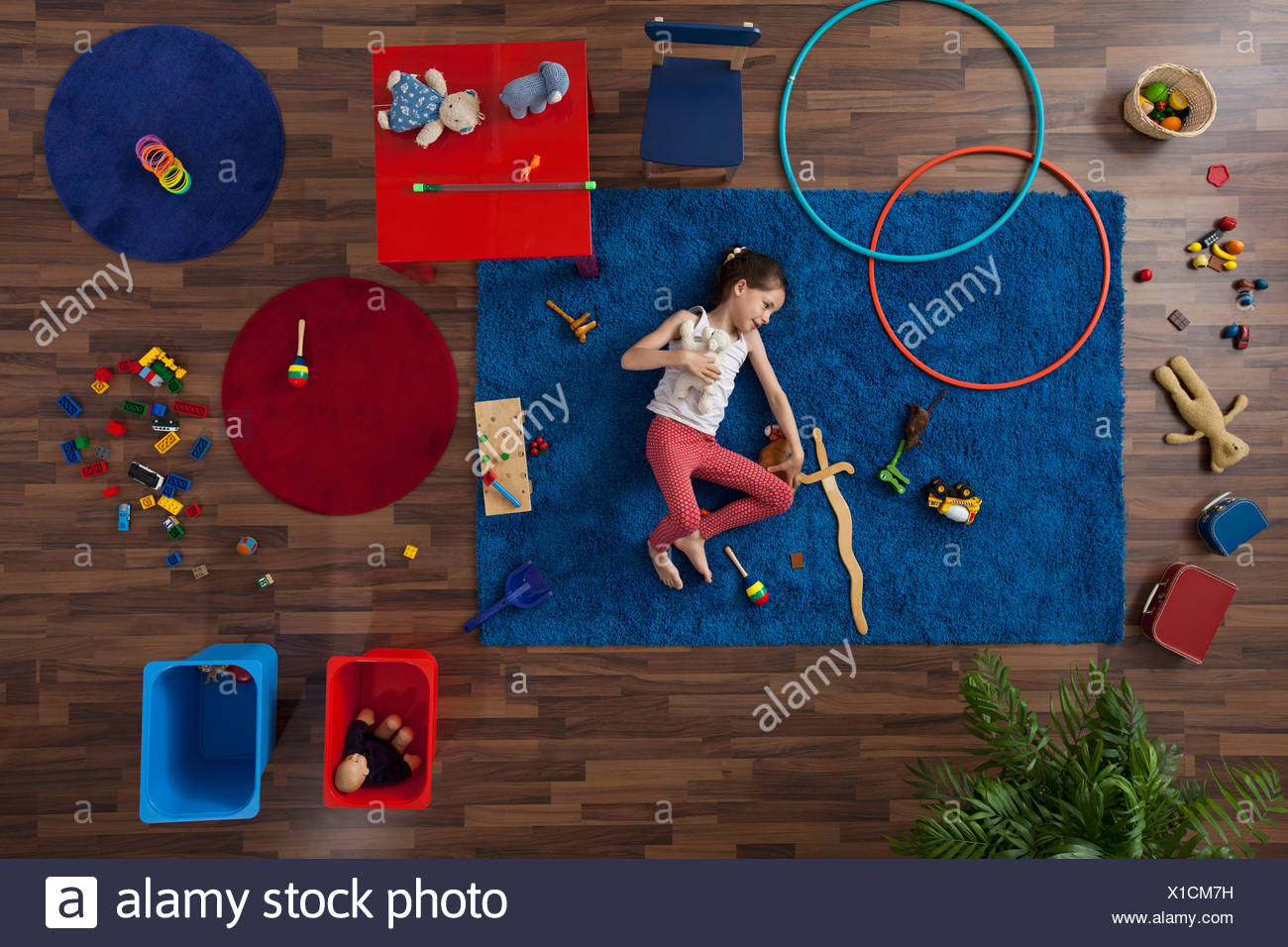 A little girl lying on a rug with toys, overhead view Stock Photo