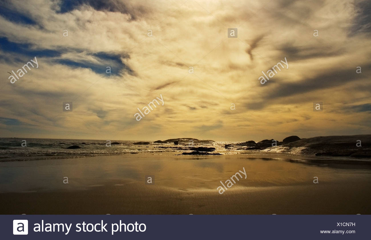 Sand and ocean at sunset - Stock Image