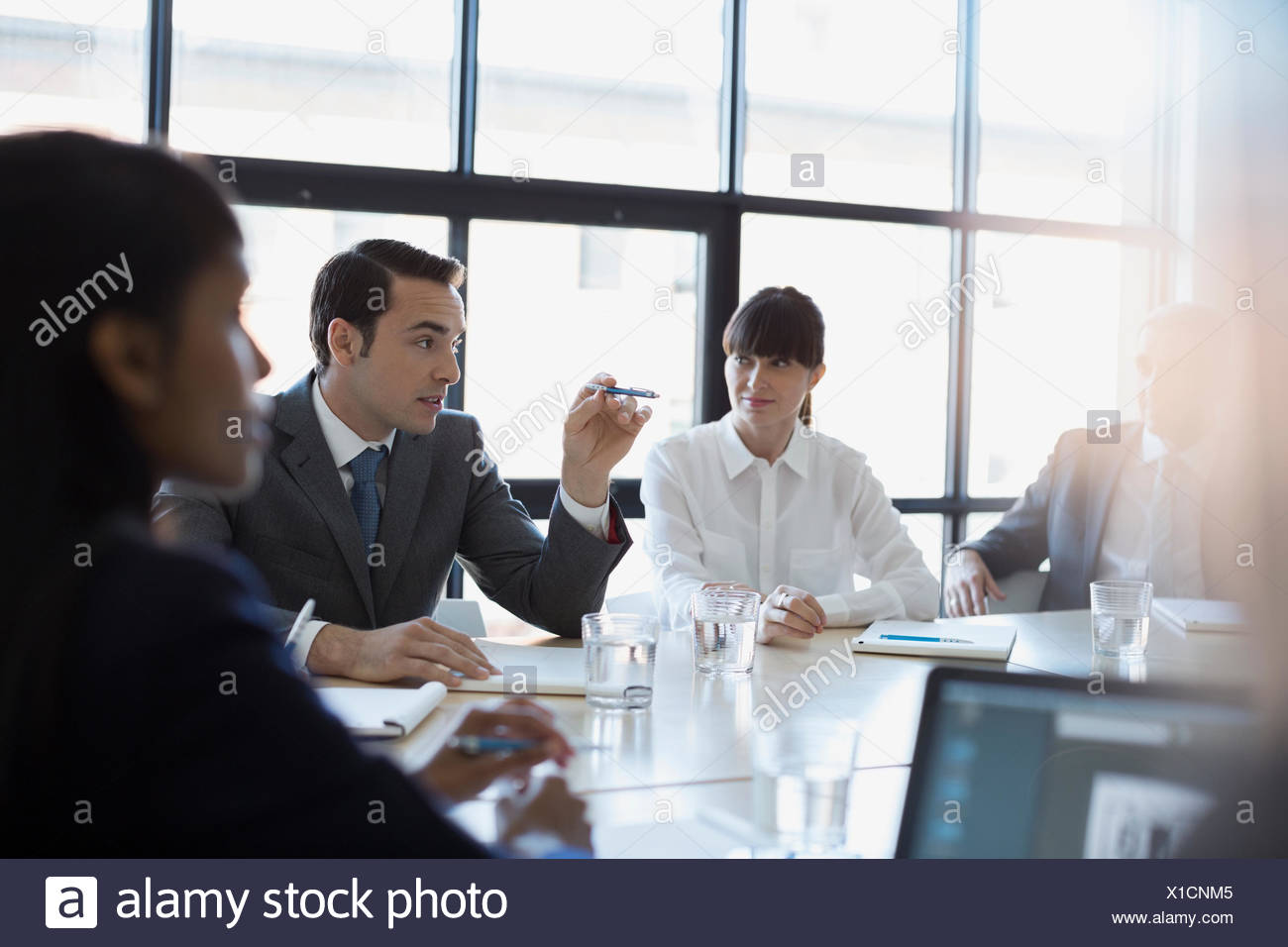 Businessman gesturing and explaining in conference room meeting - Stock Image