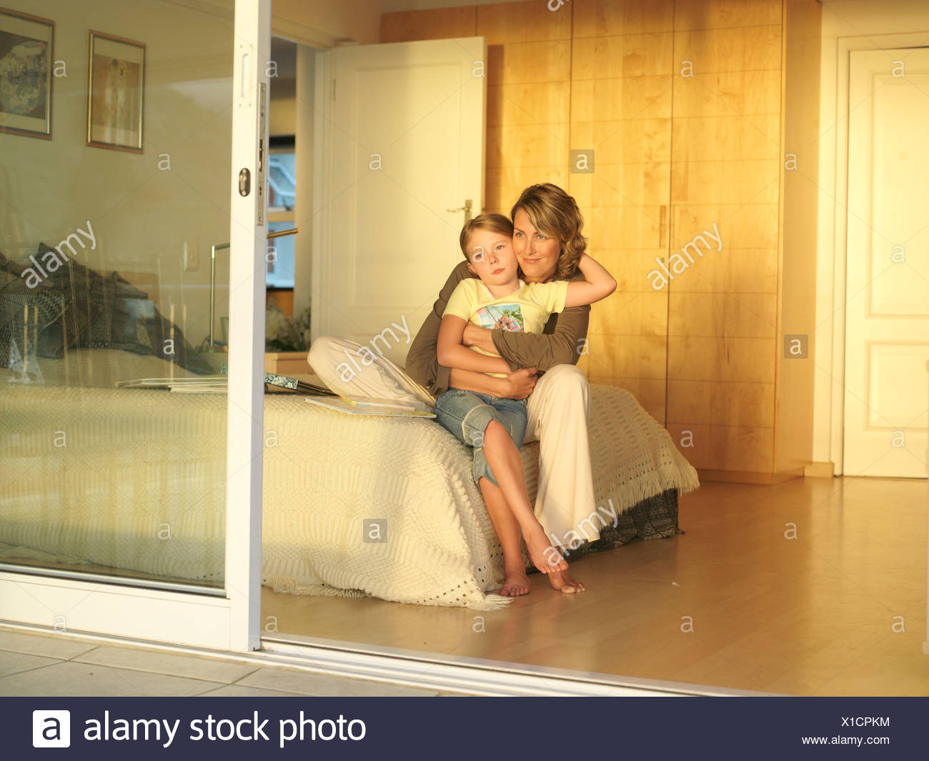 Mother and daughter 6 8 sitting on edge of double bed view through open sliding doors & Mother And Daughter Hugging Door Stock Photos u0026 Mother And Daughter ...