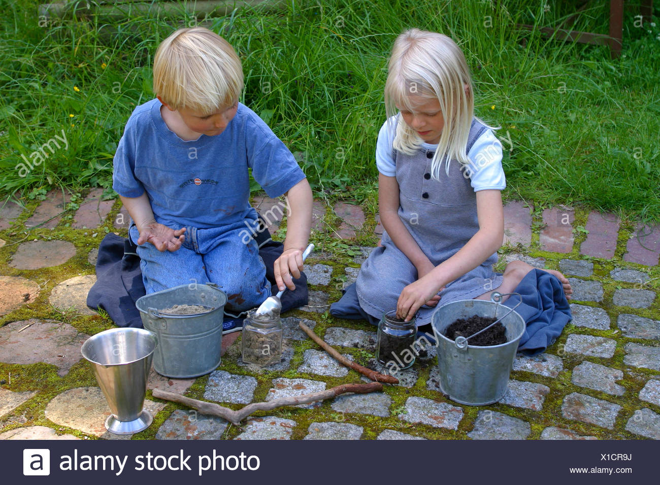 two children mixing soils to paint with earth colour, Germany - Stock Image