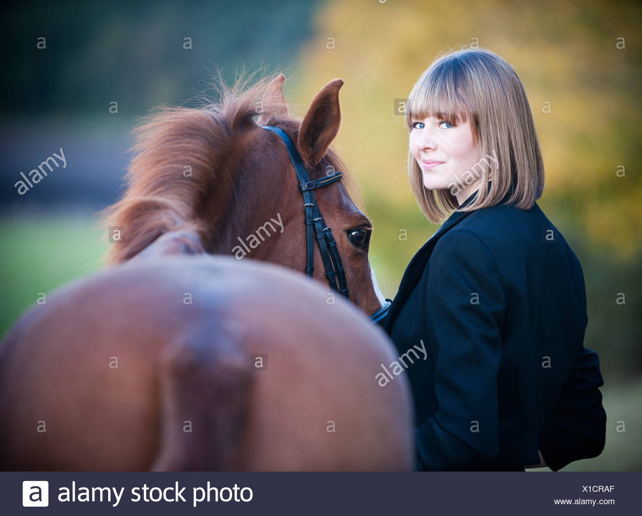 A woman leading a bay horse by the bridle. - Stock Image