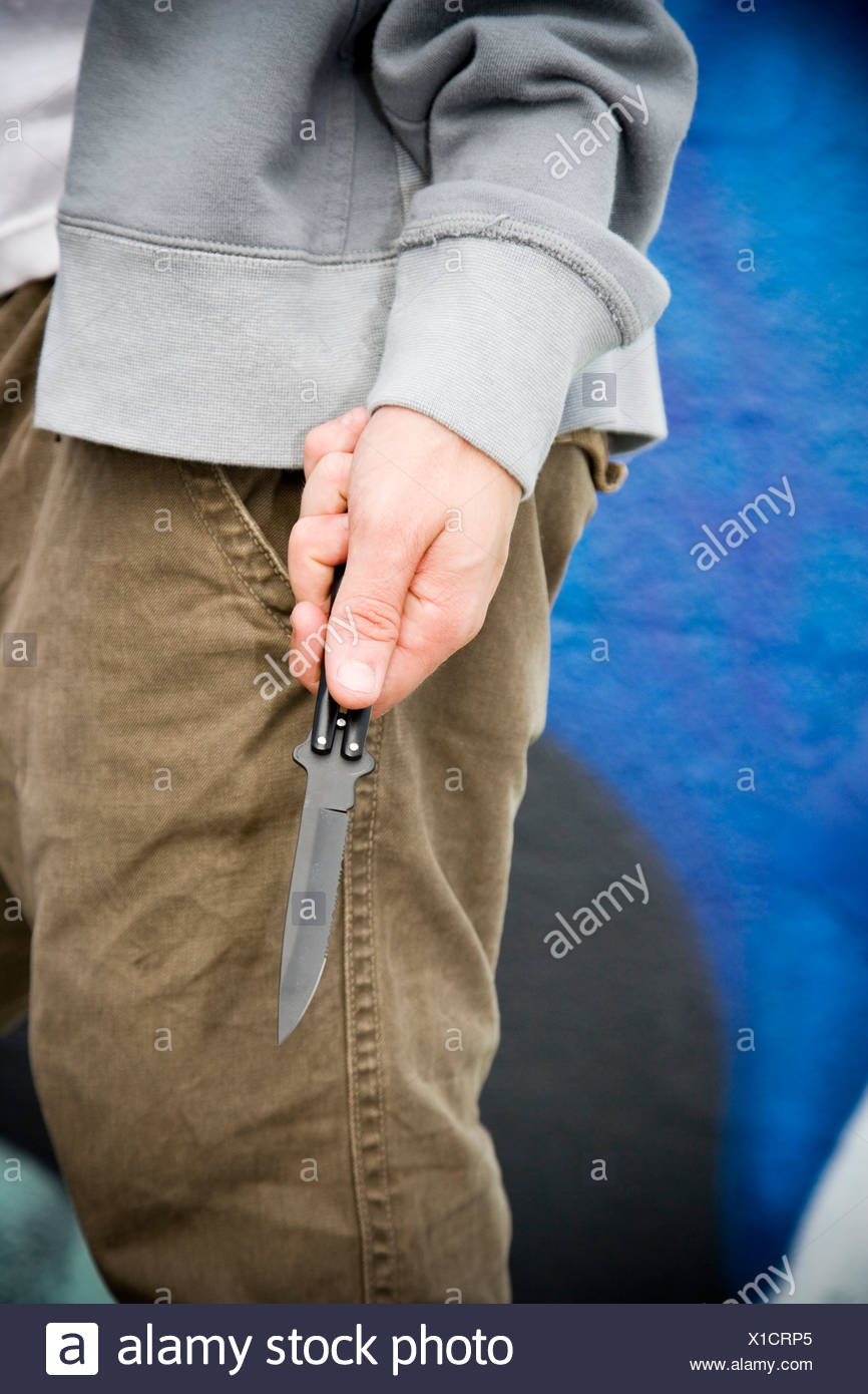Close up of a young man holding a knife - Stock Image
