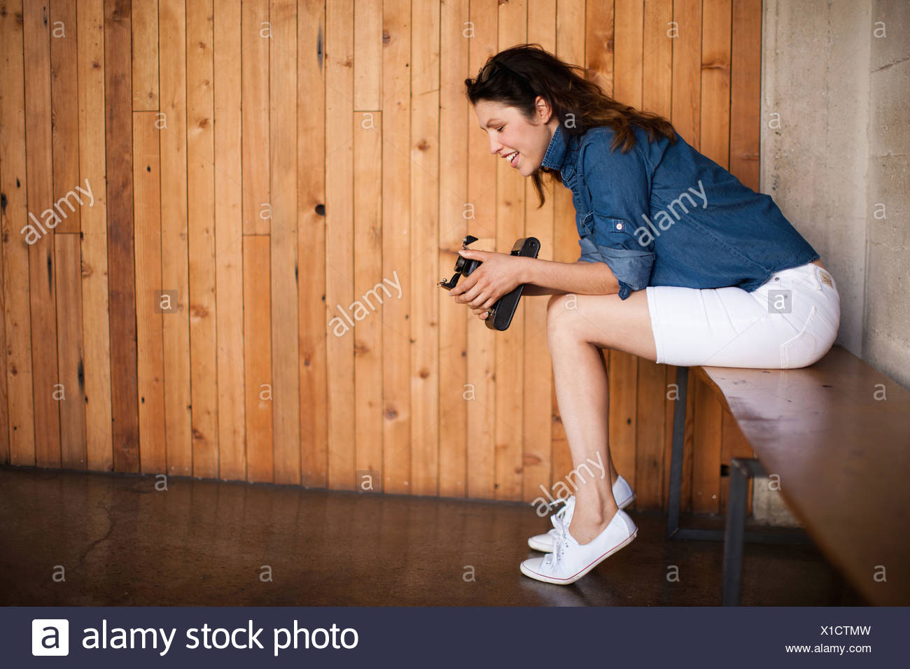 Mid adult woman using vintage medium format camera - Stock Image