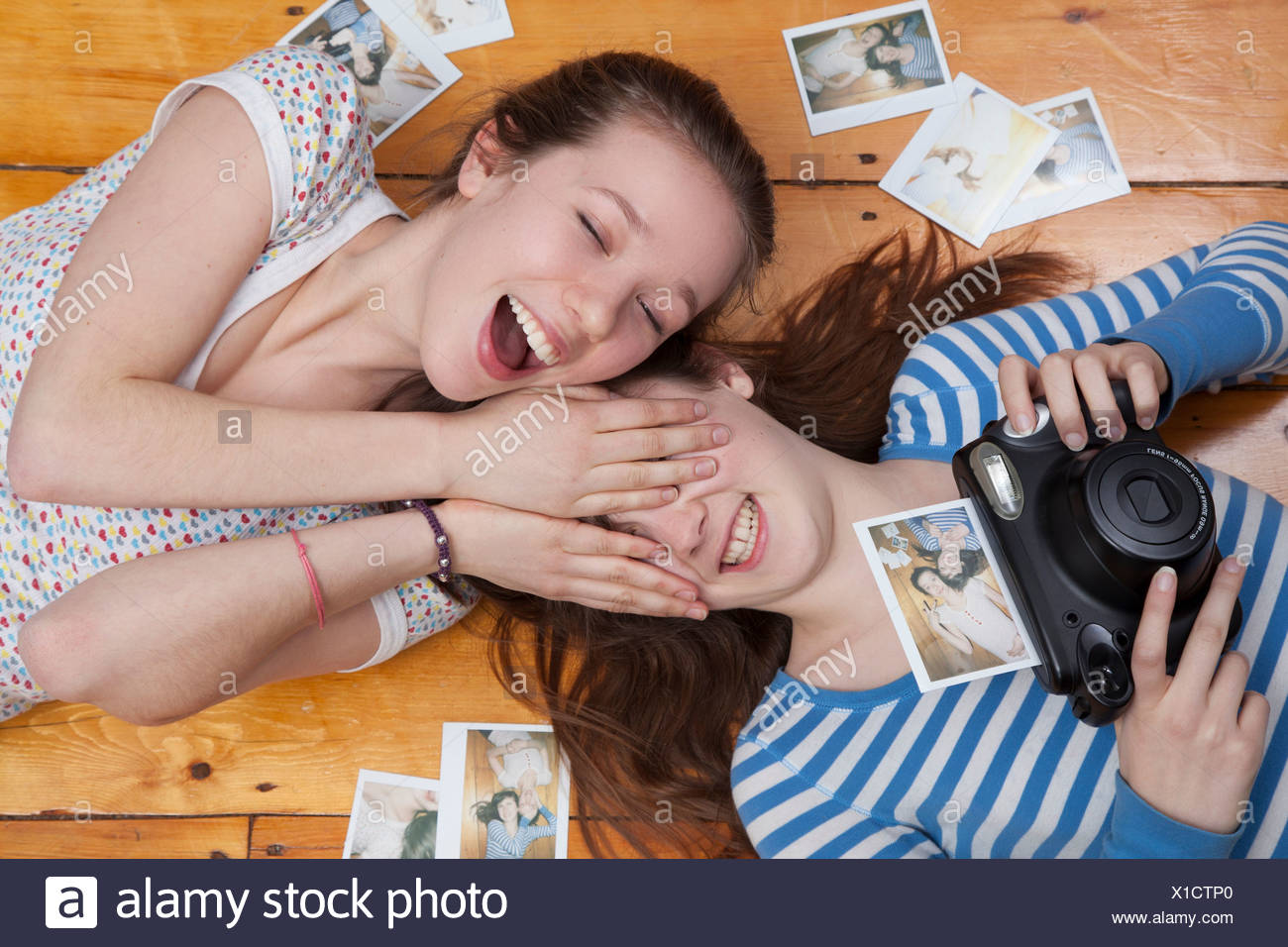 Girls lying on floor with camera, surrounded by photographs - Stock Image