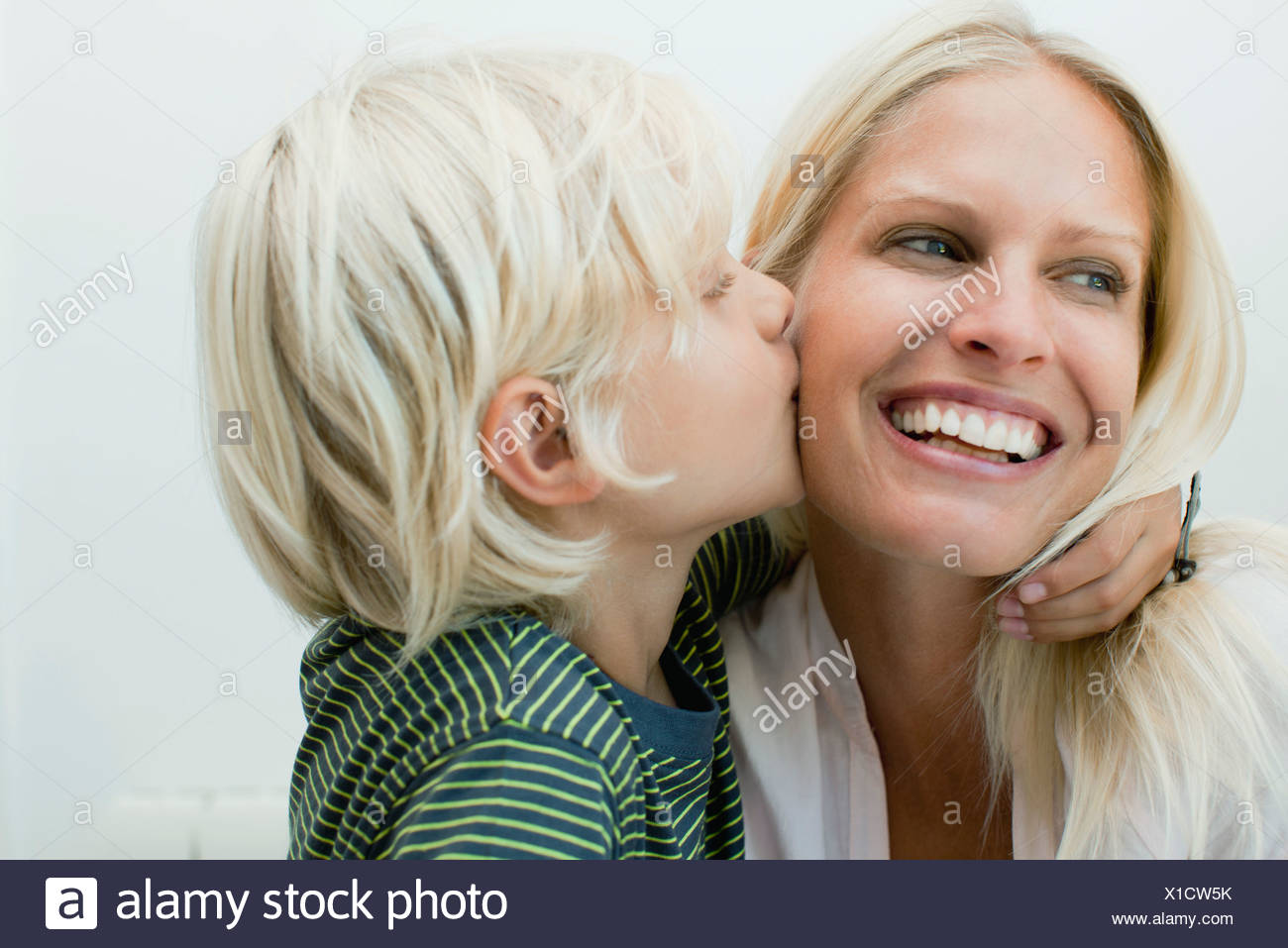 Boy kissing his mother on the cheek - Stock Image