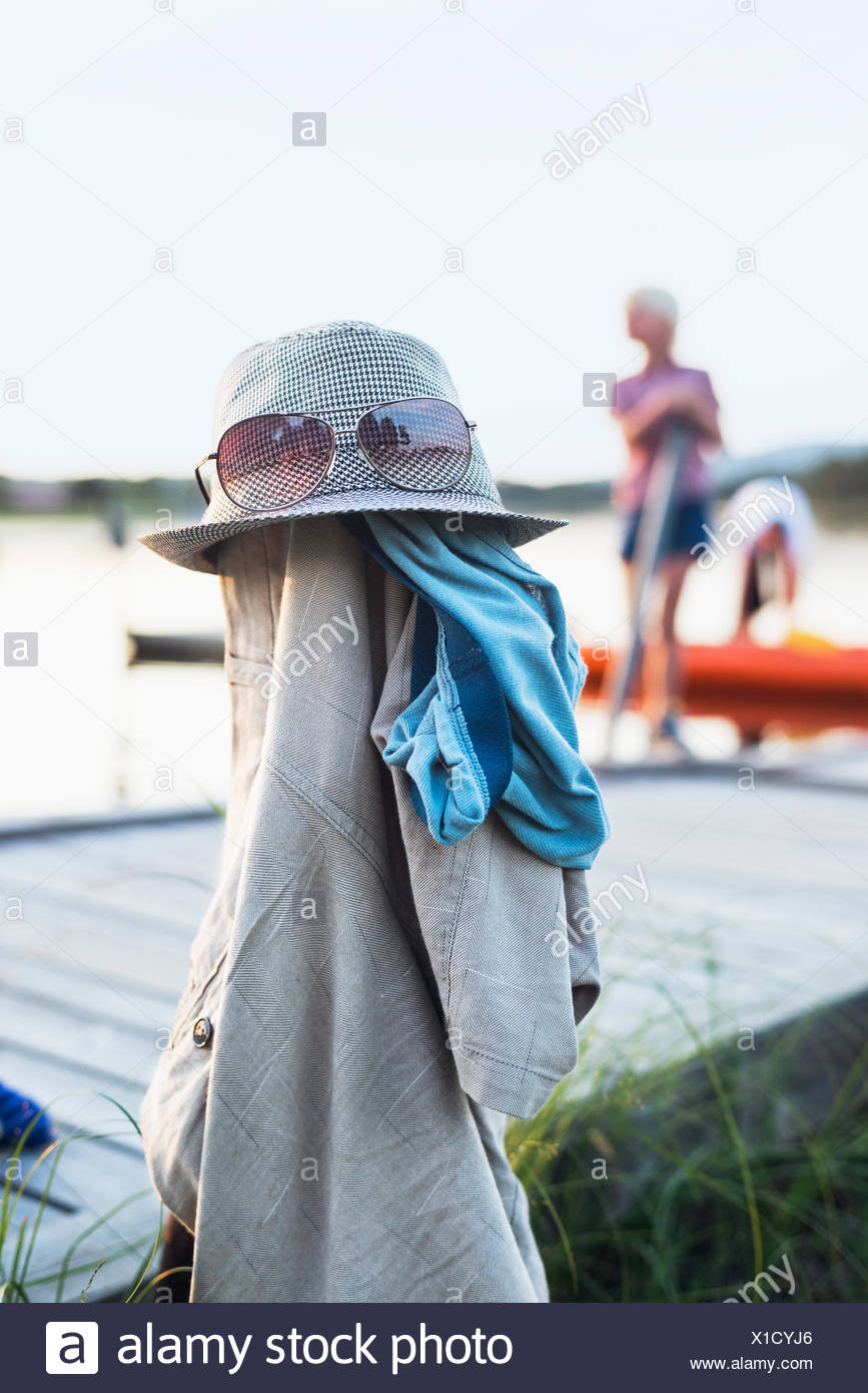 Clothes and sunglasses on pole at lake - Stock Image
